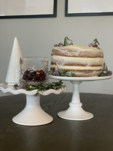 White cake stands with naked spice cake and sugared cranberries.